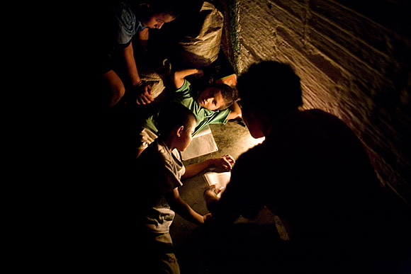 photograph of children studying by candlelight